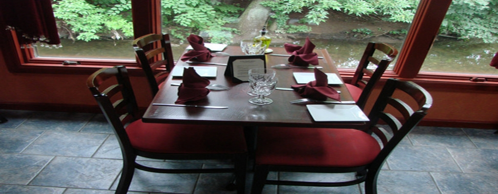 Tables for two or four overlooking a serene stream